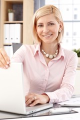 Happy female office worker with laptop computer
