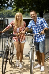 Happy sporty casual couple going for bicycle ride
