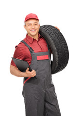 Manual worker holding a clipboard and a tire