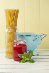 The ingredients to cook spaghetti: pasta, tomato and a strainer