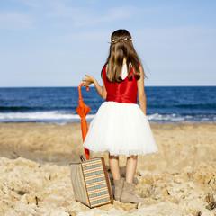 Niña con maleta y paraguas rojo de espaldas en el mar
