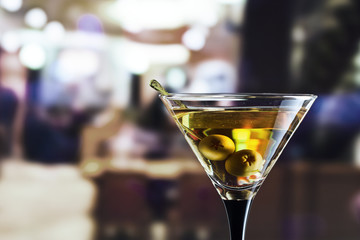 glass with martini and green olives