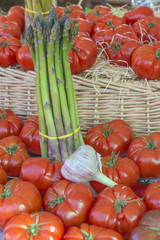 Asparagus, tomatoes, and garlic on display on a market stall