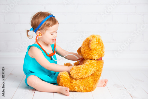 girl playing doctor and treats teddy bear - 81294989