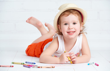 happy little artist  girl in a hat draws pencil