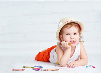 happy dreamy little artist  girl in a hat draws pencil