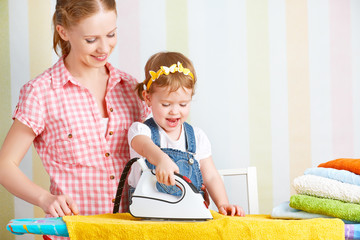 family mother and baby daughter together engaged in housework ir