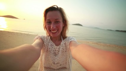 Young happy woman on beach taking selfie at sunset