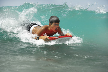 Teenager catching a wave, a surfboard