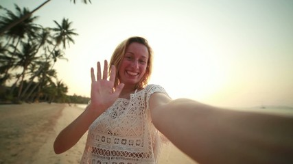 Beautiful young woman on beach taking selfie at sunset