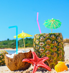 close up of pineapples and coconuts by the shore