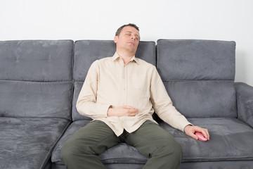 Goodlooking man in causal wear sleeping on sofa.