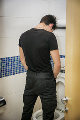 Rear View of a Young Man Peeing at the Toilet