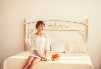 beautiful girl sitting on a bed with a bouquet and looking away