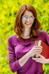 red-haired smiling young woman with books