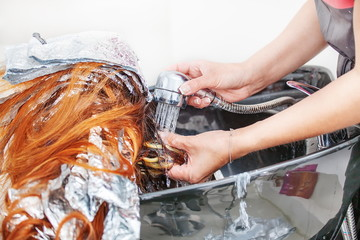 Barber girl washing her hair a client