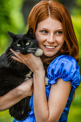 red-haired smiling young woman with black cat