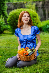 young woman in sitting on lawn with vegetable basket