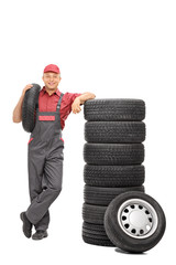 Male worker carrying a tire