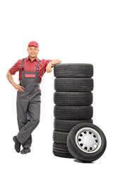 Handsome male mechanic leaning on a stack of tires