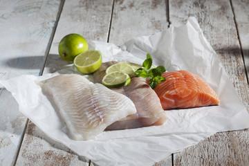 Fischfilet, Schellfisch, Seelachs, Lachs, Limetten, auf Papier