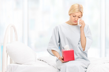 Sad female patient crying seated on a hospital bed