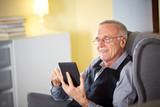 Senior man at home reading on a e-book 2