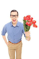 Romantic young man holding a bunch of red tulips
