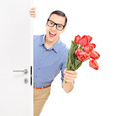 Man entering a room with bunch of red tulips