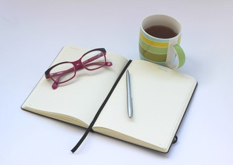 Blank open notebook with cup of tea and pen