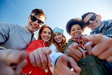 happy teenage friends pointing fingers on street
