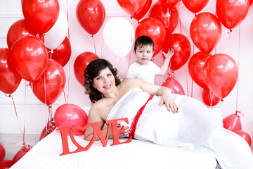Pregnant woman and her son on a bed,love sign, red balloons