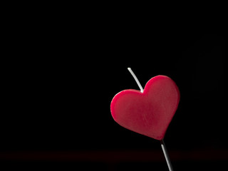 Heart shaped candle. Black background