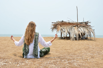 Young woman meditating on Rajbag beach of South Goa. India