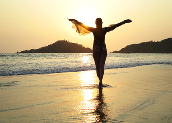 Young woman meditating on Palolem beach. South Goa, India