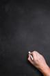 Hand mit Kreide vor leerer Kreidetafel