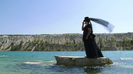 Woman In Black Standing On Cliff  on the Pond
