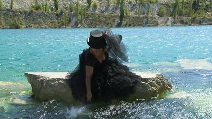 Woman In Black Splashing Water  on the  Lake