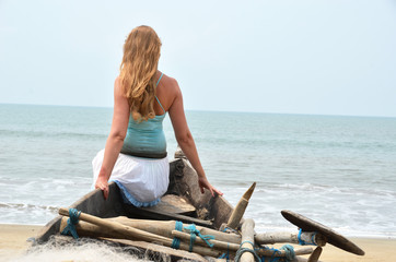 Girl sitting on the old fishing boat. Rajbag beach of South Goa,