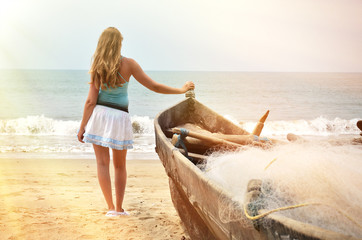 Girl at the old fishing boat looking to the ocean. Rajbag beach