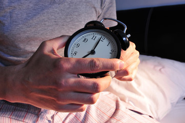 young man in bed setting the alarm clock