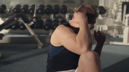 Endurance man doing abdominal exercises on floor