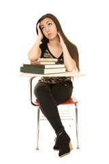 Attractive female student sitting at desk looking up