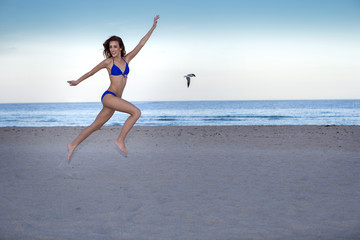 Young cheerful woman in bikini jumping on the beach.