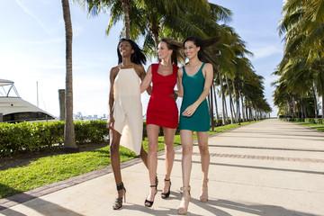 Three women walking, on a warm sunny summer day.