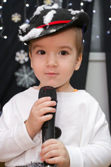 Adorable child singing (or talking) into a microphone.