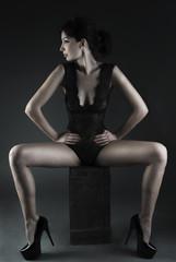 Female model sitting in a studio - dark background.