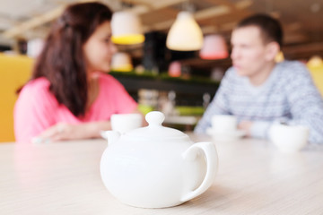 Closeup white kettle. Beautiful young couple drinking tea