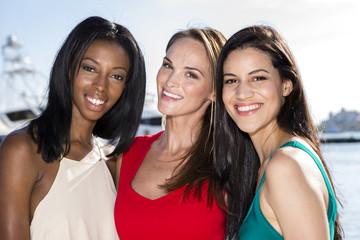 Three women posing in marina harbor, yachts on background.