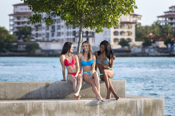 Three women sitting in marina harbor.
